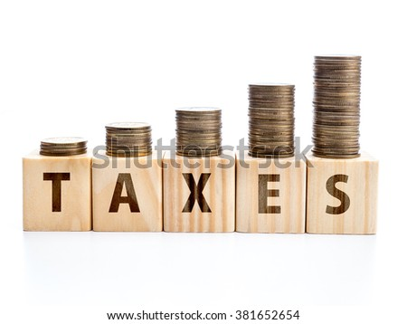 Piles of coins arranged in increased manner placed on wooden block with TAXES word - stock photo