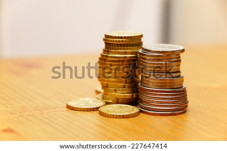 Piles of coins on a wooden table - stock photo