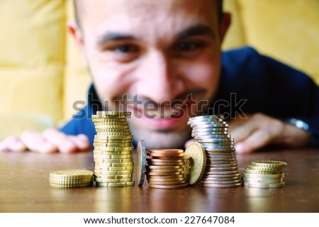 Piles of coins with a happy man looking at it - stock photo