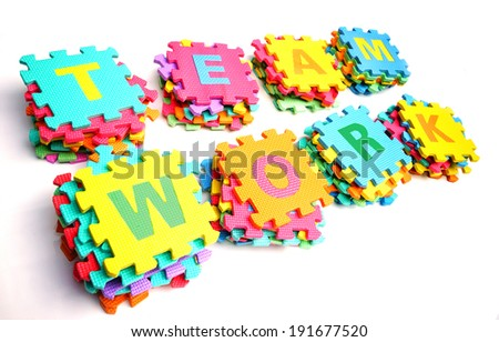 piles of colorful jigsaws arranged as the word teamwork    - stock photo