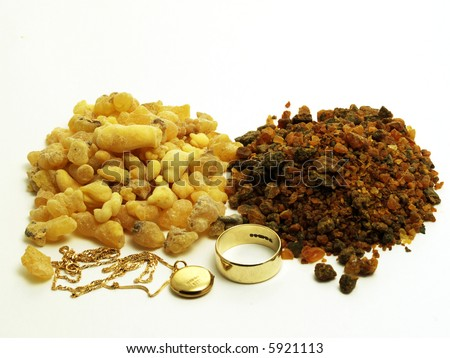 Piles of frankincense and myrrh with gold jewelery isolated on white