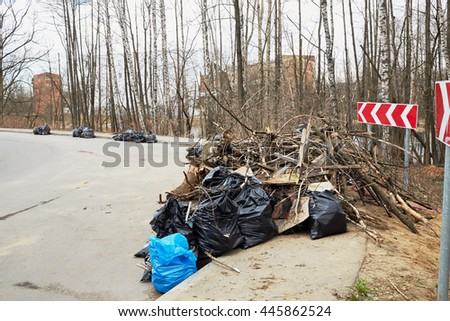 Piles of garbage bags and dead trees along edge of the road. - stock photo