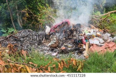 Piles of garbage being burned on the side of streets