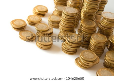 piles of golden coins on white background, mexican ten pesos coins - stock photo