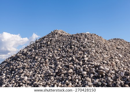 Piles of Gravel at Construction Site under Bright Blue Sky - stock photo