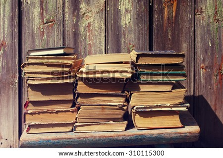 Piles of old books. Old books against an ancient wooden wall - stock photo