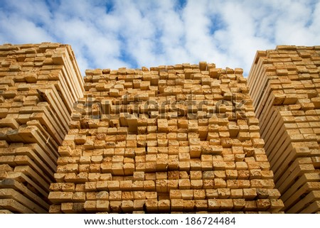 Piles of stacked rough cut lumber at a sawmill - stock photo