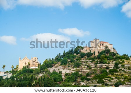 Pilgrimage church of Sant Salvador on green hill in Arta village, Mallorca island, Spain. Beautiful landsacape with medieval architecture, green trees and blue sky with clouds on a sunny day. - stock photo