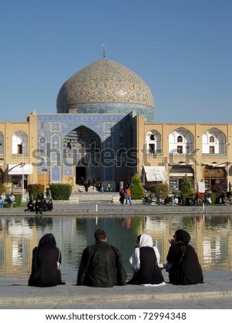 Pilgrims sitting opposite the Sheikh Lotfallah Mosque in Iran - stock photo