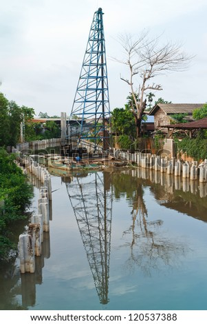 Piling rigs located along riverbanks. - stock photo