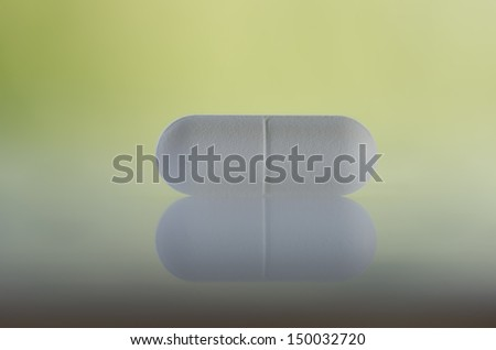 Pill against green background - stock photo