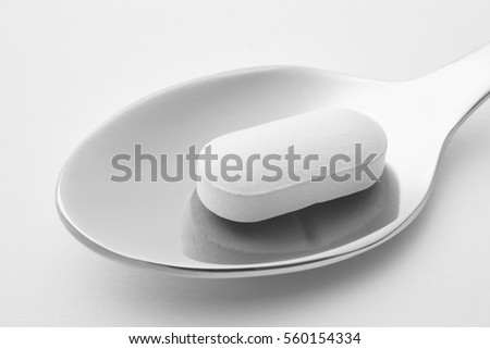 Pill and spoon detail. White background. Medicament treatment. Health care photo