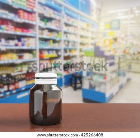 Pill bottle on table top on blurred pharmacy, Pharmacy in shopping mall, Pharmacy in shopping center, Shopping drug and pill at pharmacy in holiday,  Pharmacist and clinic, Medicine for health care - stock photo