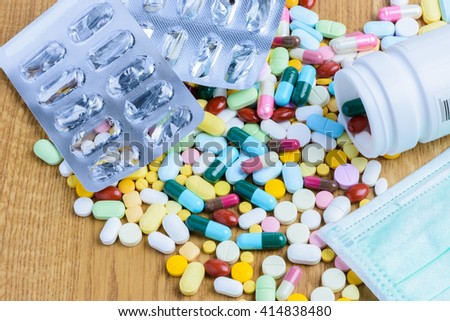 Pill bottle spilling pills and empty blister pack on to surface wooden background