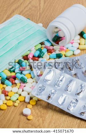 Pill bottle spilling pills and empty blister pack on to surface wooden background - stock photo