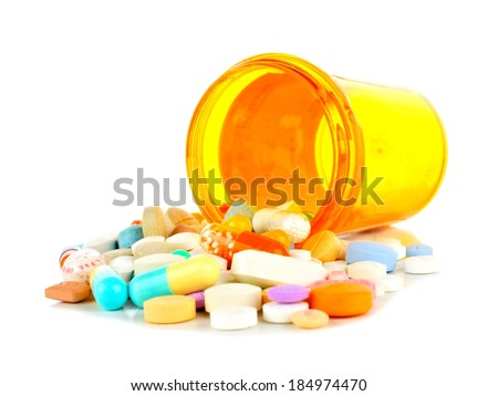 Pill bottle with spilling medications over white - stock photo