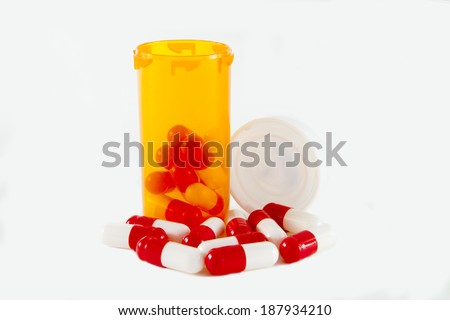 Pill bottles and capsules against a white background - stock photo