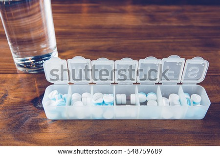 Pill box with a drug on table