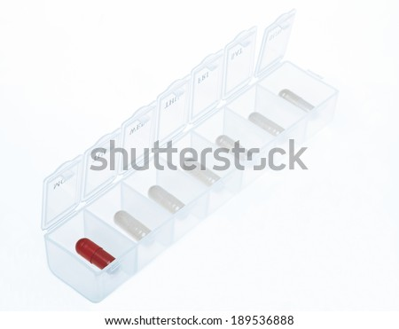 Pill box with white pills and only one red pill. - stock photo