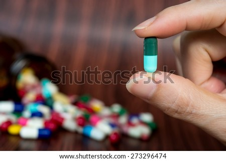 Pill in hand and assorted pills