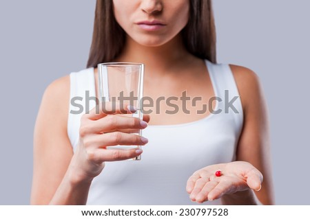 Pill in her hand. Cropped picture of young woman holding a glass with water and pills in her hands - stock photo