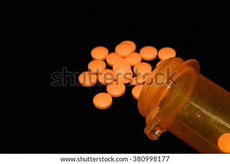 Pill spilling out of pill bottle isolated on black background