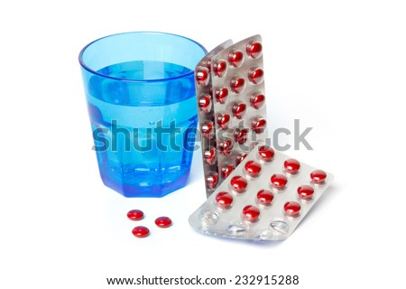 Pill strips and a blue glass with water against white background - stock photo
