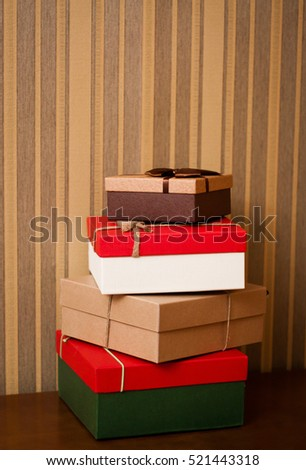 Pillar of boxes with presents. Group of presents. Gifts box on brown table. Colorful gifts box.