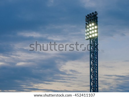 Pillar spotlights football field in the background  sky cloud.