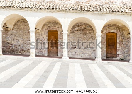 Pillars of a roofed stone aisle in Tuscany