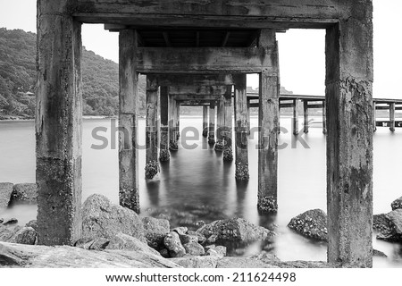 Pillars of the Harbour Bridge./Black and white photo shows the old pillars and the movement of water. - stock photo