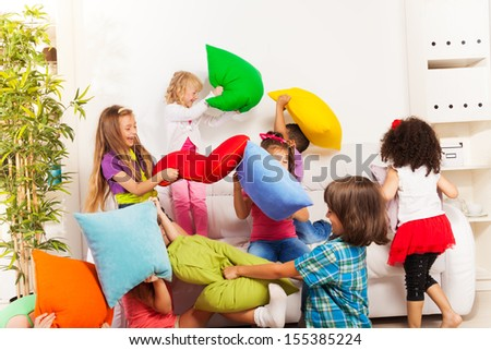 Pillow fight - large group of kids actively playing with pillow in the living room on the coach