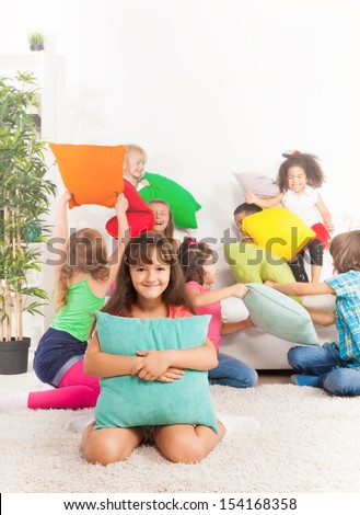 Pillow fight - on happy little Caucasian girl with pillow and her friends fighting on background