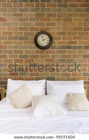 Pillows and bed in bedroom with brick wall - stock photo