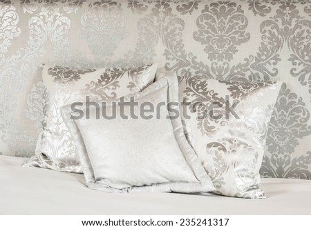 Pillows on a hotel bed. There are white satin pillows with silver pattern on it. Image taken as a closeup.