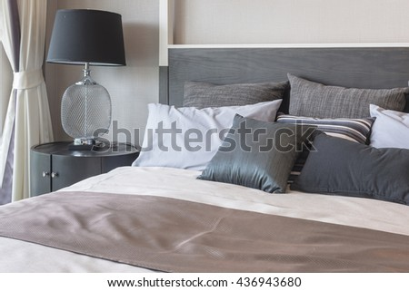 pillows on bed and luxury black lamp style on wooden table side in bedroom design