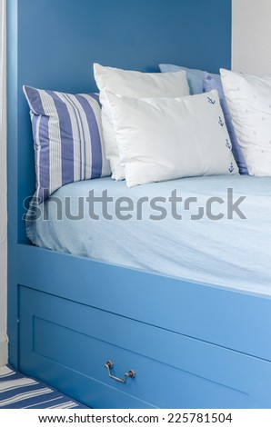 pillows on blue bed in kid bedroom - stock photo