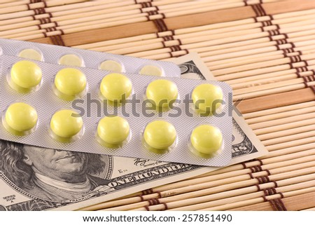 Pills and american money close-up background - stock photo