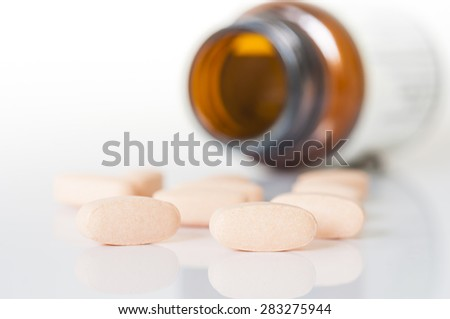 Pills and bottle on the white background.