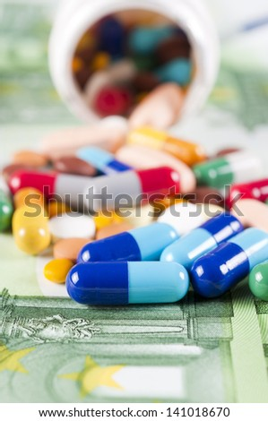 Pills and capsulas splashed on one hundred euro bills - stock photo