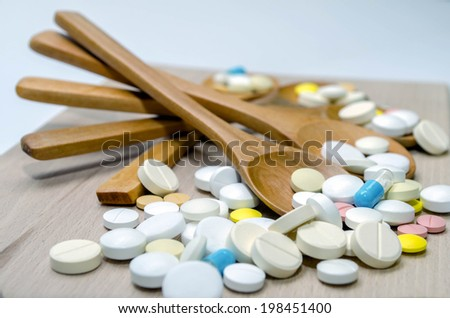 Pills and capsule with wooden spoon on wood background