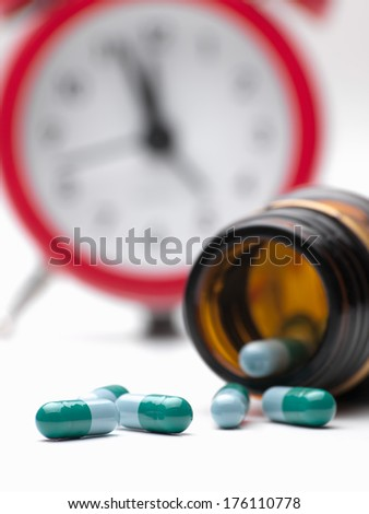 Pills  and clock  over white background,closeup, for health care,medicine,addiction themes - stock photo