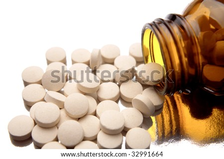 Pills and glass bottle on white