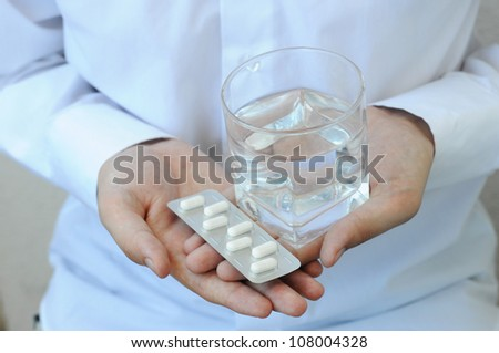 Pills and glass of water in man's hand, closeup view