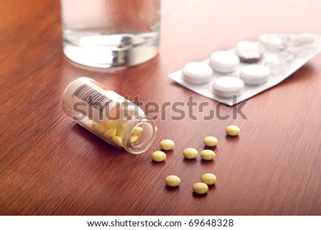 Pills and glass of water on table