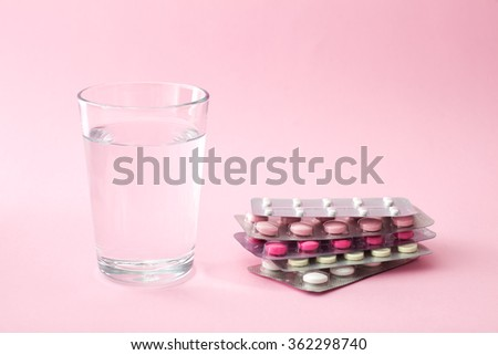 Pills and glass of water with copy space - stock photo