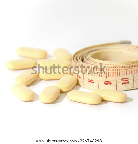pills and measuring tape on a white background