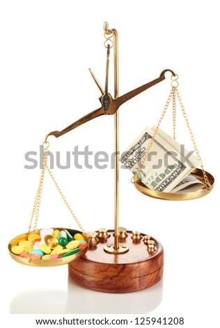 Pills and money in scales isolated on white - stock photo