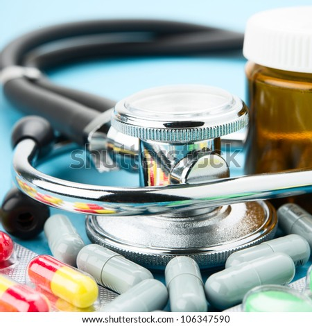 Pills and stethoscope on blue background