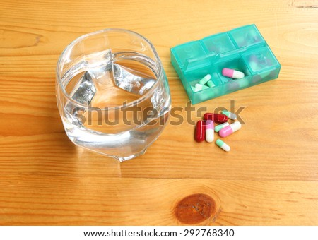 Pills and tumbler on wood table - stock photo